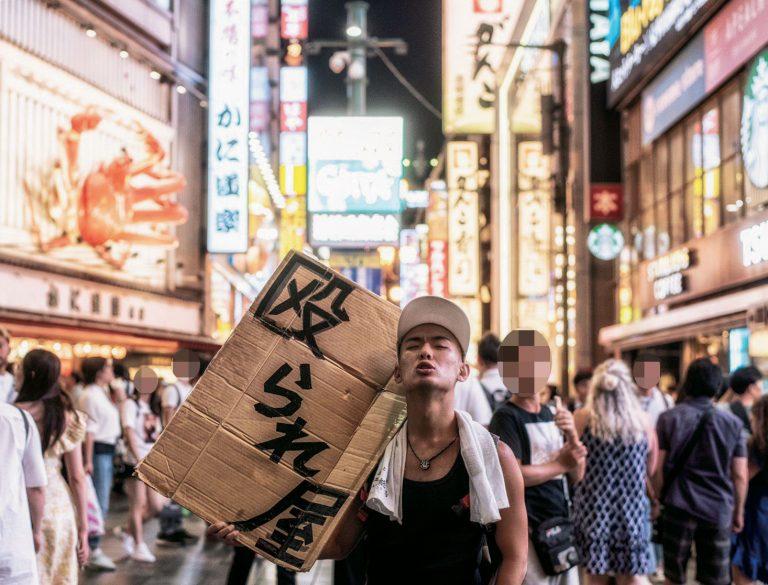 បុរសម្នាក់ឈរស្រែកតាមដងផ្លូវ Shinjuku អោយគេវាយដើម្បីរកប្រាក់